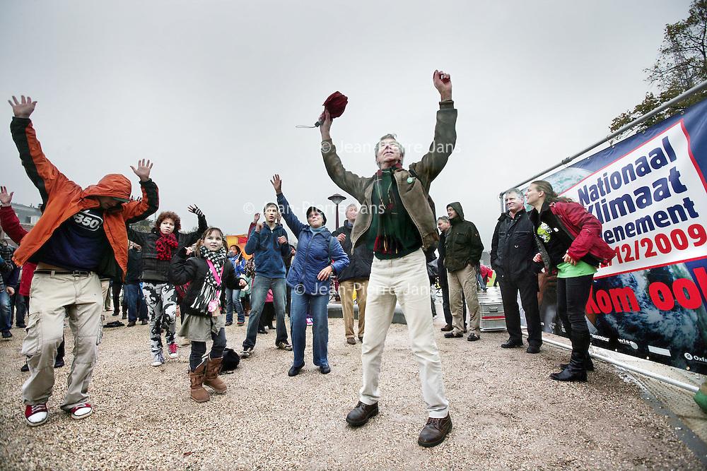 Nederland, Amsterdam , 24 oktober 2009..Vanuit heel Amsterdam kwamen mensen vandaag op het Museumplein bijeen om de charleston te dansen, te bewegen en gezamelijk het getal 350 te vormen..In een symbolische en originele actie werd premier Balkenende opgeroepen om zich op het terrein van de klimaatverandering als een sterke leider op te werpen.Het evenement was een van de ruim 4000 gelijktijdig gegouden acties in 172 landen, georganiseerd door 350.org, in wat de massaalste mondiale klimaatactiedag uit de geschiedenis is geworden..Wetenschappers zijn de afgelopen jaren tot de conclusie gekomen dat 350 CO2-deeltjes per miljoen de hoogste veilige bovengrens voor de atmosfeer is. De huidige CO2 concentraties bedraagt 390 ppm. .International day of climate action. Scientists in recent years concluded that a safe atmosphere contains a maximum of 350 parts per million CO2. The current CO2 concentration is 390 ppm. Climate activists dansed a symolic danse on the Museumplein in Amsterdam together with many others in other countries.