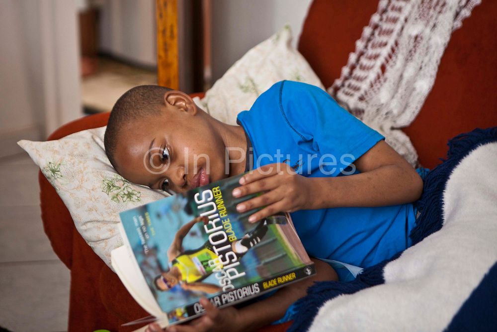Kutlwano is a young South African boy who has recently had both legs surgically amputated after developing a severe deep vein thrombosis (DVT).  He has recently been discharged from hospital back to his family home. He is lying on a sofa reading a book about Oscar Pistorius given to him by Bigshoes Foundation.  Soweto, Gauteng, South Africa.