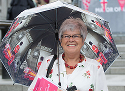 Trafalgar Square, London, June 12th 2016. Rain greets Londoners and visitors to the capital's Trafalgar Square as the Mayor hosts a Patron's Lunch in celebration of The Queen's 90th birthday. PICTURED: A woman watches the events on stage.
