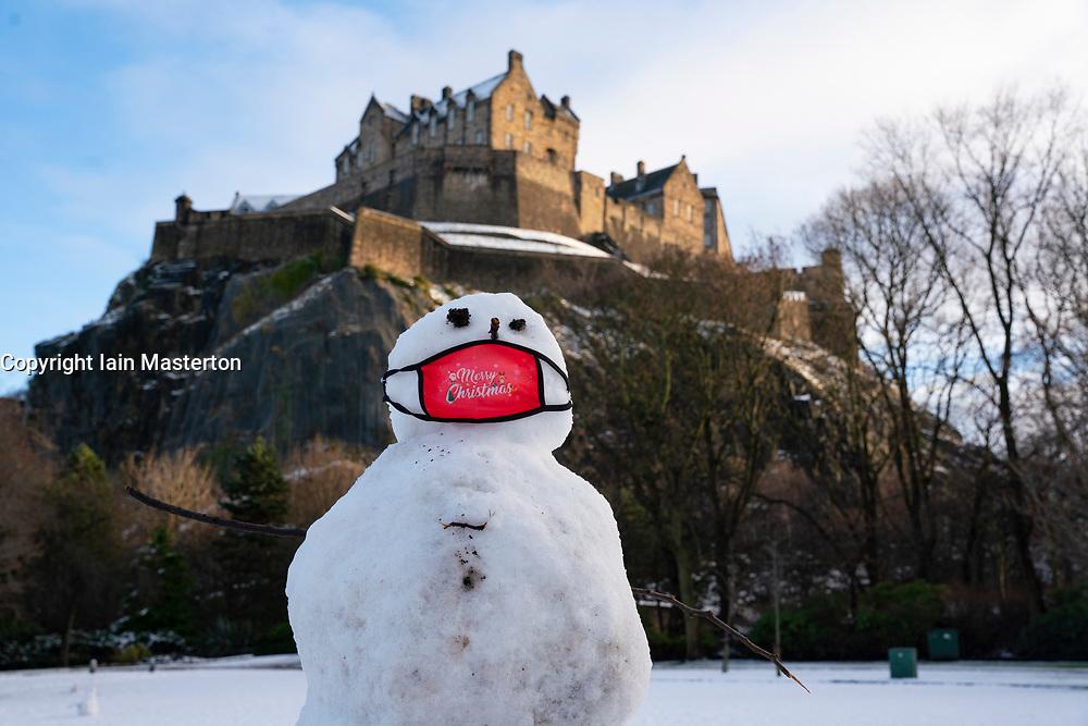 Edinburgh, Scotland, UK. 29 December 2020. A snowman wearing a facemask has been built in Princes Street gardens below Edinburgh Castle following overnight snow in the city. Iain Masterton/Alamy Live News