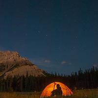 Sitting below the Big Dipper and Cascade Mountain, a camper admires moonlit scenes in Banff National Park, Alberta, Canada.
