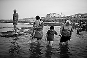 """Children being taken for the """"holy bath"""" in the sea during the St. Bartolomeu celebration. The """"holy bath"""" is believed to drive away evil and cure diseases related with """"demonic possession"""", such as stuttering or epilepsy. This tradition that dates back to the sixteenth century (1566), and it claims the devil is on the loose during this day. Every year on 24 August  faith and tradition join thousands of people at the feast of St. Bartolomeu do Mar, for ritual that mixes the sacred and the profane."""