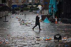 © Licensed to London News Pictures.  12/07/2021. London, UK. A member of the pubic walks through piles of rubbish left behind  football supporters in central London as England lost to Italy on penalties during yesterday's EURO 2020 final. Photo credit: Marcin Nowak/LNP