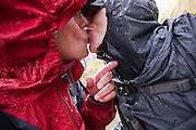 Parmenter and Liana Welty kiss in the rain, dressed in wet rain jackets,  on a backpacking trip in the Skolai Pass area of Wrangell-St. Elias National Park, Alaska.