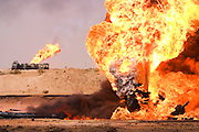 Heading north through the Rumaila Oil Field of Southern Iraq, convoys of fuel trucks carry the army's mechanical lifeblood past burning oil wells set ablaze by retreating Iraqi forces. The Rumaila field is one of Iraq's biggest oil fields with five billion barrels in reserve. The burning wells in the Rumaila Field were ignited by retreating Iraqi troops when the US and UK invasion began in March 2003. Many of the wells are 10,000 feet deep and produce huge volumes of oil and gas under tremendous pressure, which makes capping them very difficult and dangerous. Rumaila is also spelled Rumeilah.