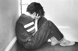 Young boy sitting on floor in corner of room with head in hands,