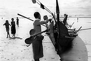 Fisherman prepares his boat on the beach. Maungmakan township.  South East Burma 1998