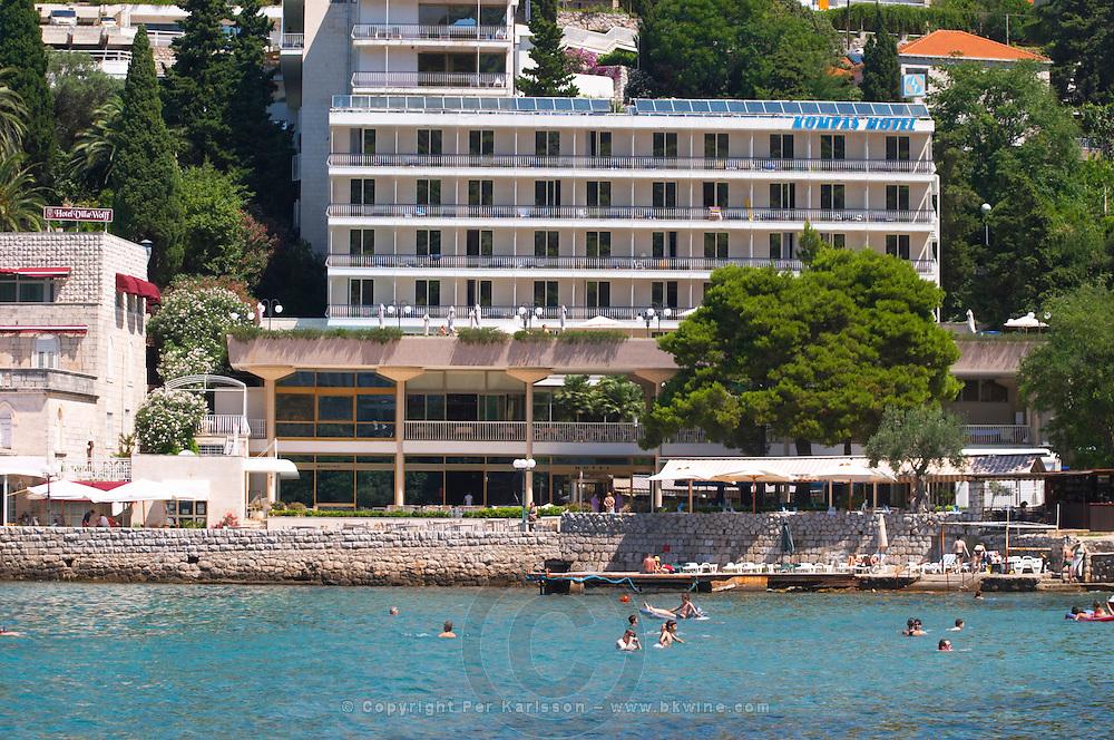 Hotel, restaurant with terrace, sea and beach, people swimming. Hotel and restaurant Kompas. Uvala Sumartin bay between Babin Kuk and Lapad peninsulas. Dubrovnik, new city. Dalmatian Coast, Croatia, Europe.