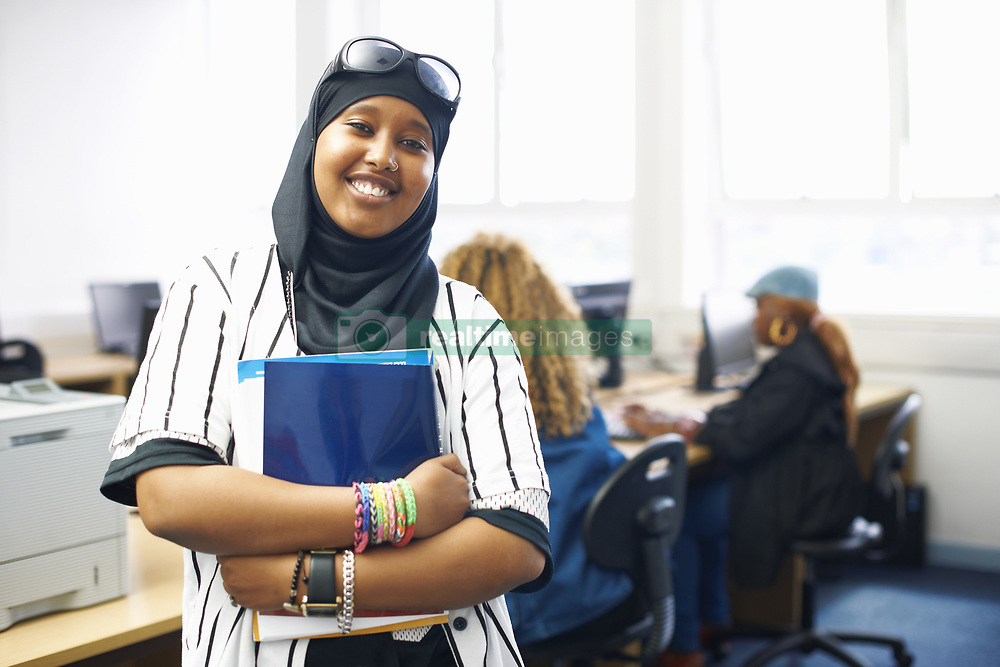 June 25, 2014 - Portrait of young female student with file in college classroom (Credit Image: © Image Source/Image Source/ZUMAPRESS.com)