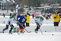"""Local teams REMax Hackers and the Puck Nuts go for the puck during first round """"Just for Fun"""" division at Meredith Bay during the New England Pond Hockey Classic Friday morning.  (Karen Bobotas/for the Laconia Daily Sun)"""
