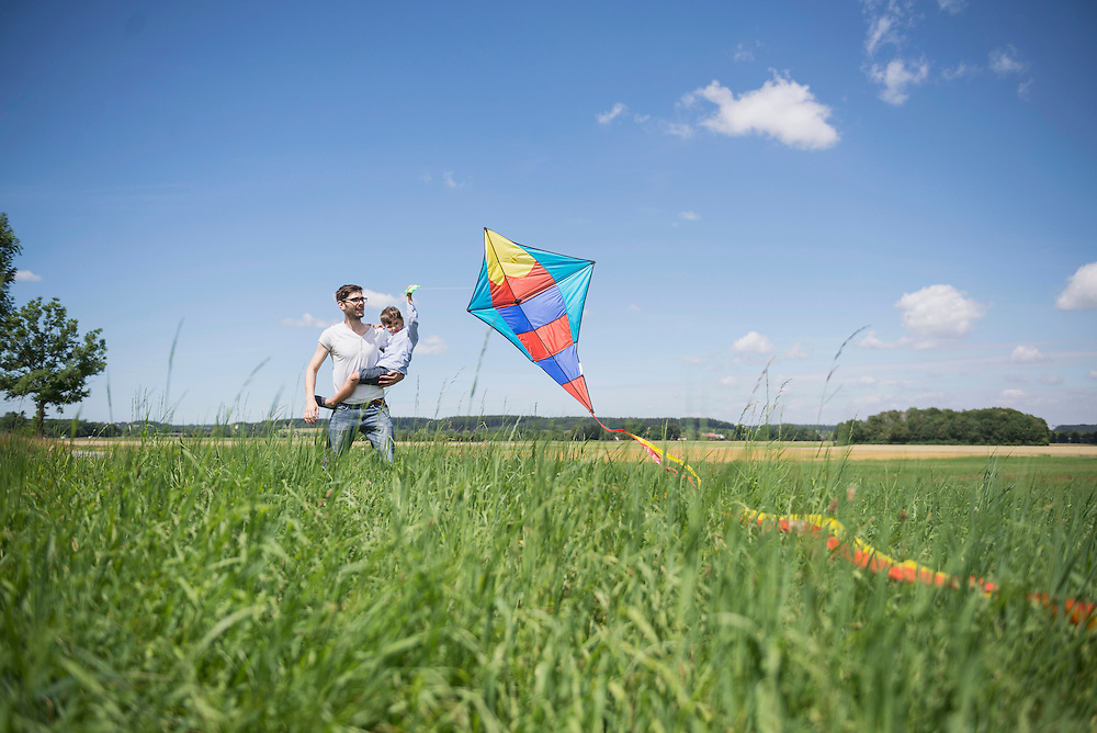 Father and his son flying kite in the countryside, Bavaria, Germany