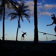 Tight rope walkers silhouetted against the late afternoon sky, practice at Ipanema beach. Rio de Janeiro,  Brazil. 4th July 2010. Photo Tim Clayton..The beaches of Rio de Janeiro, provide the ultimate playground for locals and tourists alike. Beach activity is in abundance as beach volley ball, football and a hybrid of the two, foot volley, are played day and night along the length and breadth of Rio's beaches. .Volleyball nets and football posts stretch along the cities coastline and are a hive of activity particularly at it's most famous beaches Copacabana and Ipanema. .The warm waters of the Atlantic Ocean provide the ideal conditions for a variety of water sports. Walkways along the edge of the beaches along with exercise stations and cycleways encourage sporting activity, even an outdoor gym is available at the Parque Do Arpoador overlooking the ocean. .On Sunday's the main roads along the beaches of Copacabana, Leblon and Ipanema are closed to traffic bringing out thousands of people of all ages to walk, run, jog, ride, skateboard and cycle more than 10 km of beachside roadway. .This sports mad city is about to become a worldwide sporting focus as they play host to the world's biggest sporting events with Brazil hosting the next Fifa World Cup in 2014 and Rio de Janeiro hosting the Olympic Games in 2016...