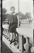 woman posing on a bridge railing 1920s