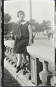 woman posing on a bridge railing 1920s