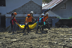 OCTOBER 10, 2018 - Poso, Indonesia - Indonesian search and rescue team carry a plastic bag containing dead body at Petobo in Poso, Central Sulawesi Province, Indonesia. Disaster agency has put the figure of casualties in the Indonesian multiple-strong quakes and an ensuing tsunami on September 28 to 2,010 people with over 5,000 others remaining missing. (Credit Image: © Zulkarnain/Xinhua via ZUMA Wire)