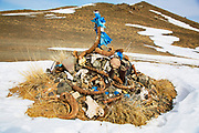 A Mongolian ovoo, a sacred pile of stones, prayer flags and offerings used as shrines or alters throughout Mongolia, Gobi Desert, Mongolia