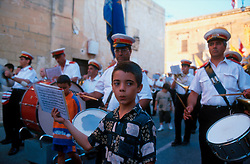 MALTA GOZO SANNAT JUL00 - A boy holds the notes for his drumming father marching behind during the procession at the Sannat Fiesta.. . jre/Photo by Jiri Rezac. . © Jiri Rezac 2000. . Tel:   +44 (0) 7050 110 417. Email: info@jirirezac.com. Web:   www.jirirezac.com