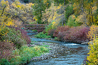 The Provo River slowly flows down the canyon surrounded by the remaining colors of Fall.