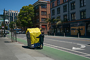 A man moves his shelter to a designated Safe Sleeping Site parking lot in San Francisoc, CA on June 23, 2020, after local authorities cleared out the alley where he lived. Many unhoused residents were given 1-2 hours notice before having to relocate.
