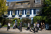 Colourfully painted house on Pembridge Road in Notting Hill, West London, England, United Kingdom. People enjoying a sunny day out hanging out at the famous Sunday market, when the antique stalls line the street.  Portobello Market is the worlds largest antiques market with over 1,000 dealers selling every kind of antique and collectible. Visitors flock from all over the world to walk along one of Londons best loved streets.