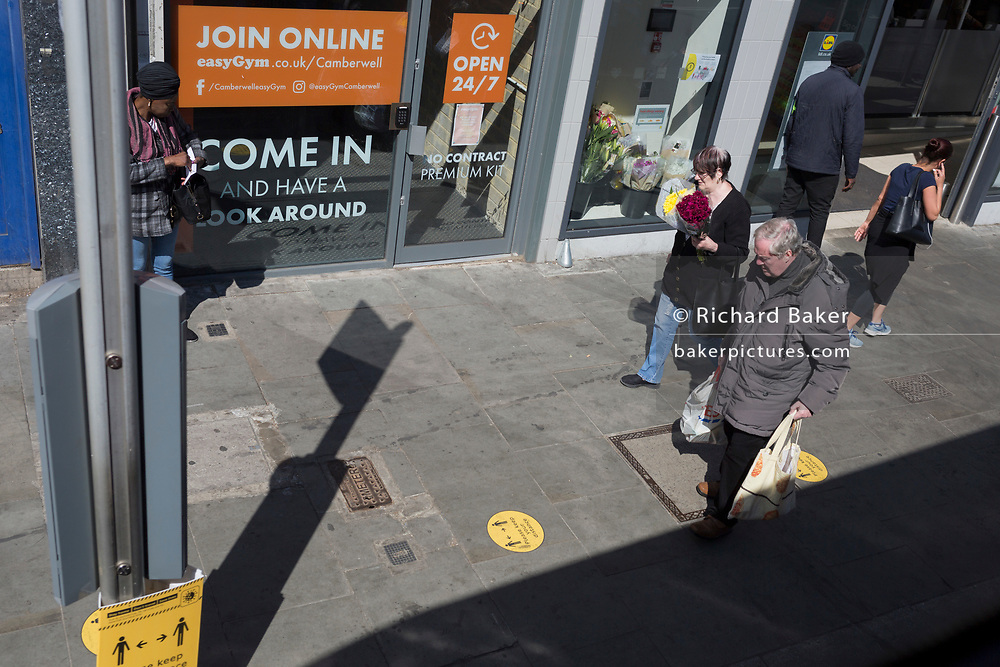 As the UK's Coronavirus death toll during the government's social distancing lockdown, rose by 384 to 33,998, and the R rate of infection is reported to be between 0.7 and 1.0, south Londoners go about their business with social distancing marks on the ground on the high street in Camberwell, on 15th May 2020, in London, England.