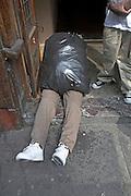 Visual joke of body hidden in plastic bin bag with legs showing