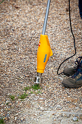 Using an electric heated weeder to destroy weeds in gravel