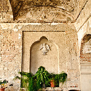 Part of the open-air cloisters of Iglesia de San Francisco, a Spanish colonial church in Antigua, Guatemala. Ornate decorations are carved into the roof, but over time the elements have started to take over.