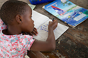 One of Linna Kinabo's grandchildren doing her homework.<br /> <br /> Linna set up and runs a poultry business selling both eggs and meat. <br /> <br /> She is now able to help pay for some of her grandchildren to go to school.<br /> <br /> She attended MKUBWA enterprise training run by the Tanzania Gatsby Trust in partnership with The Cherie Blair Foundation for Women.