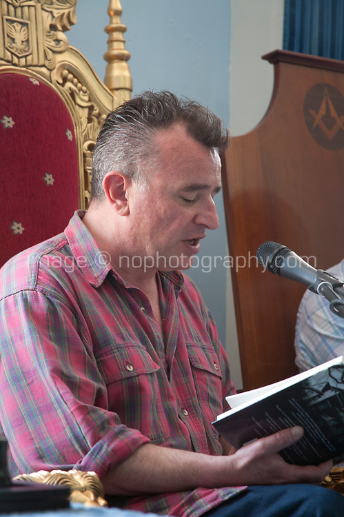 Irish crime writer Declan Hughes reads from his lbook during a discussion on 'Emerald Noir', current Irish crime fiction at the Dalkey Book Festival, Dalkey, County Dublin, Ireland. Saturday 21st June 2014.
