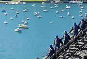Tourists descending the main arch of the Sydney Harbour Bridge, boats moored in Lavender Bay in the background. Sydney, Australia