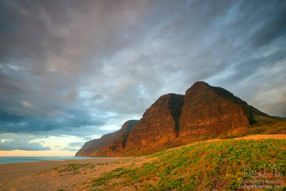 The setting sun lights up several tall mountains above Barking Sands beach in Polihale State Park, Kauai, Hawaii. The tallest of the mountains is more than 1,600 feet (488 meters) tall. From right to left, the peaks are: Mana Ridge, Kolo Ridge, Lapa Ridge, and Haeleele Ridge. The remote beach is located at the western-most point of the island of Kauai.