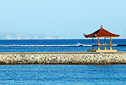Beachside pagoda with waves breaking over reef and the cliffs of Penida island in the background. Sanur Beach, Bali, Indonesia.