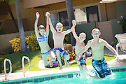 Happy Kids Jumping into the Pool