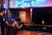 WASHINGTON, USA - August 19: A father watches as his son tries to shoot out a star on a piece of paper with an air rifle at the Montgomery County Agricultural Fair in Gaithersburg, Md., USA on August 19, 2017.