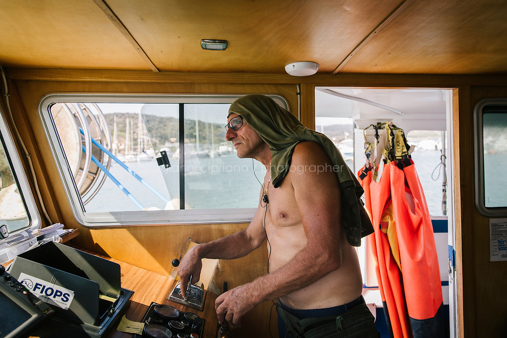 """TALAMONE, ITALY - 27 AUGUST 2019: Fisherman and activist Paolo Fanciulli (58) is seen here saling his boat """"Sirena"""" back to the harbour in Talamone, Italy, on August 27th 2019.<br /> <br /> In 2006, fisherman Paolo Fanciulli used government funds and the donations from his loyal excursion clients to fund a project in which they protected the local waters from trawling by dropping hundreds of concrete blocks around the seabed. But his true dream was to lay down works of art down on the sea floor off the coast of Tuscany. His underwater art dreams came true when the owner of a Carrara quarry, inspired by Mr. Fanciulli's vision, donated a hundred marble blocks to the project.<br /> Mr. Fanciulli invited sculptors to work the marble and set up kickstarter accounts, boat tours and dinners to fund the project. The acclaimed British artist Emily Young carved a ten-ton """"Weeping Guardian"""" face, which was lowered with other sculptures into the water in 2015.<br /> Since then, coral and plant life have covered the sculptures and helped bring back the fish. And Paolo the Fisherman is catching as many of them as he can."""