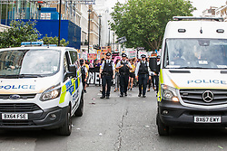 London, UK. 6 July, 2019. Activists from Lesbians and Gays Support The Migrants, African Rainbow Family, the Outside Project, Micro Rainbow and other LGBT+ groups are preceded by rows of stewards and police officers as they take part in a London Pride Solidarity March at the very rear of Pride in London after storming the parade in solidarity with those for whom Pride in London is inaccessible and in protest against the corporatisation of Pride in London.