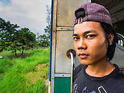 26 OCTOBER 2015 - YANGON, MYANMAR:  A man stands in the doorway on the Yangon Circular Train. The Yangon Circular Railway is the local commuter rail network that serves the Yangon metropolitan area. Operated by Myanmar Railways, the 45.9-kilometre (28.5mi) 39-station loop system connects satellite towns and suburban areas to the city. The railway has about 200 coaches, runs 20 times daily and sells 100,000 to 150,000 tickets daily. The loop, which takes about three hours to complete, is a popular for tourists to see a cross section of life in Yangon. The trains run from 3:45 am to 10:15 pm daily. The cost of a ticket for a distance of 15 miles is ten kyats (~nine US cents), and for over 15 miles is twenty kyats (~18 US cents).       PHOTO BY JACK KURTZ