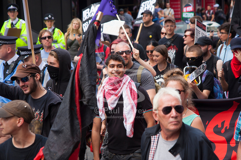 """London, June 21st 2014. A handful of masked """"anarchists"""" join the thousands strong March Against Austerity in London."""