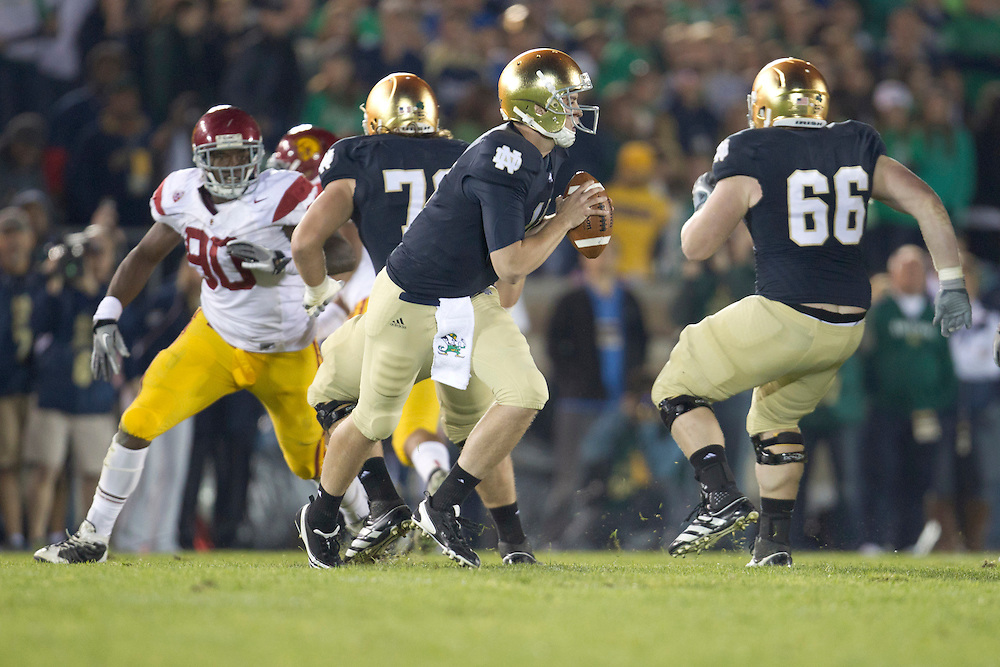 Notre Dame quarterback Tommy Rees (#11) rolls out to pass the ball during second quarter of NCAA football game between Notre Dame and USC.  The USC Trojans defeated the Notre Dame Fighting Irish 31-17 in game at Notre Dame Stadium in South Bend, Indiana.