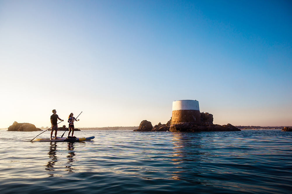 Couple paddle boarding at sunset with Icho Tower reflecting in the calm sea in Jersey, Channel Islands