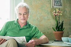 Mature man reading newspaper, smiling