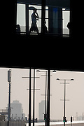 Silhouetted pedestrians on the bridge that connects Stratford's mainline station and the Westfield shopping mall near the 2012 Olympic Park.