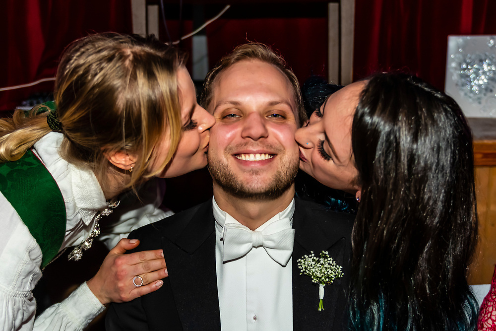 Women kissing the bridegroom at his wedding reception, Trysil, Norway.