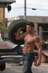 shirtless auto mechanic at a garage carrying a tire