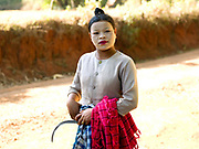 A Pa'O ethnic minority woman wearing thanakha (a traditional Burmese sunscreen and moisturiser) on her way to work on the farm, Shan State, Myanmar (Burma)