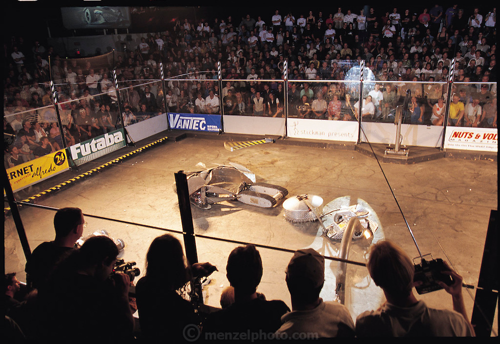 Ringed by six-foot sheets of bullet-proof glass and a sellout crowd, radio-controlled gladiators battle to the mechanical death. At Robot Wars, a two-day-long competition in San Francisco, CA the crowd roars to the near-constant shriek of metal, the crash of flying parts, and the thunderous beat of techno music. After a series of one-on-one matches, losers and winners alike duke it out in a final death-match called a Melee. In this Melee, the 13-foot Snake curls to use its drill-bit tail on its hapless victim, a tracked vehicle; meanwhile, the simple yet primitively powerful Frenzy hammers the rolling, wedge-shaped Tazbot. From the book Robo sapiens: Evolution of a New Species, page 202-203.