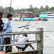 Men on a small pier fish in the Saigon River in Ho Chi Minh City, Vietnam.