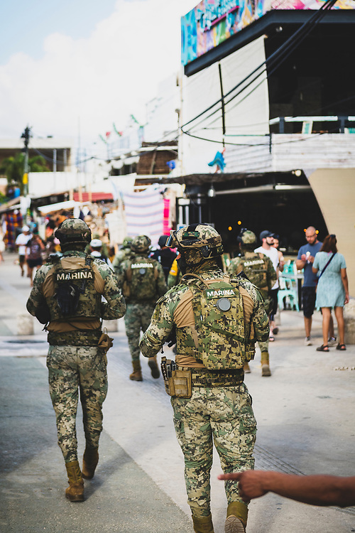 Tulum, Mexico - April 14, 2021: Several Mexican marines walk down the sidewalk on Avenida Tulum, the main road through town, during a period of increased violence, including targeted killings.