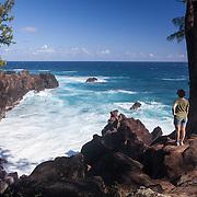 A woman stands along the coast near Manapany-Les-Bains